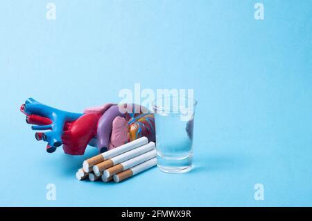 Simulate il cuore umano, le sigarette e l'alcol su uno sfondo blu. Concetto di fattori di rischio e malattie del sistema cardiovascolare a causa del fumo e.