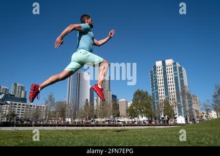 Giovane atletico che corre in città. Movimento di salto dinamico. Jogger giovane e attivo in esecuzione. Concetto di sport urbano.