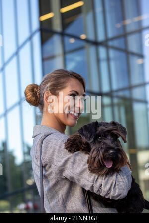 Bella giovane donna di affari che tiene il cane carino in armi dentro davanti all'edificio degli uffici