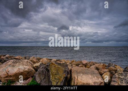 Un cielo bello e suggestivo sull'oceano. Pietre in un interruttore di onda in primo piano. Foto di Malmo, Svezia