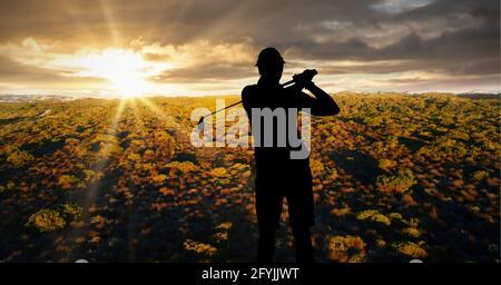 Composizione di silhouette di giocatore di golf maschile sul paesaggio e. tramonto