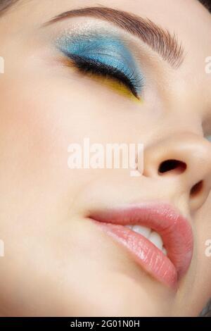 Primo piano ritratto di giovane donna con gli occhi chiusi. Macro shot closeup del viso femminile umano. Donna con il trucco di bellezza dell'occhio del Vogue della sera. Faccia con perf