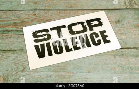 Fermare le parole di violenza sulla carta sul tavolo di legno. Concetto sociale