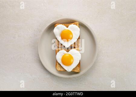 Uovo a forma di cuore in una fetta di pane di segale tostata su un piatto di ceramica. Il design della colazione è molto apprezzato. Panino sano. Pranzo festivo o colazione. Giorno dell'uovo.