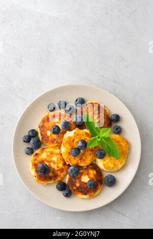 Torta al formaggio Cottage con mirtilli e menta in un piatto su sfondo grigio