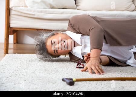 Donna anziana asiatica che cade sul tappeto e sdraiata sul pavimento in soggiorno a casa, concetto di Cascate degli adulti più anziani