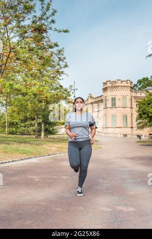 giovane ragazza che corre lungo una strada del parco e un castello sullo sfondo