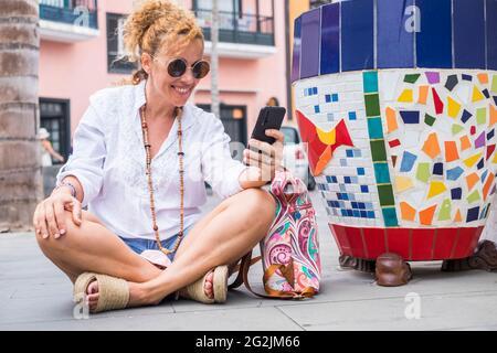 Allegra giovane donna turistica che si abbona a terra in città e utilizzare la connessione wireless wi-fi gratuito iwith telefono fare una videochiamata conferenza con gli amici - persone e felice stile di vita all'aperto