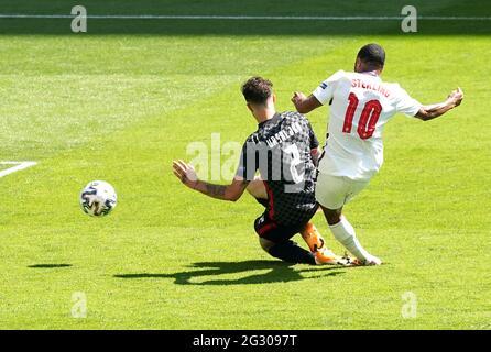 Il Raheem Sterling (a destra) dell'Inghilterra segna il primo gol della partita durante la partita UEFA Euro 2020 Group D al Wembley Stadium di Londra. Data immagine: Domenica 13 giugno 2021.