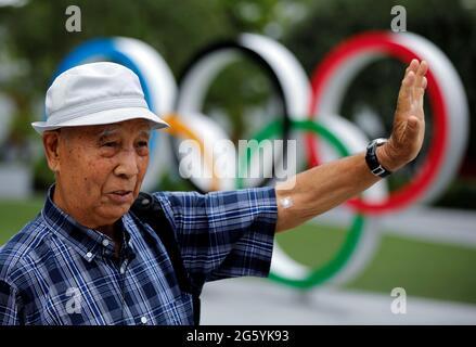Kohei Jinno, 87 anni, costretto a lasciare la sua casa due volte prima delle Olimpiadi del 1964 e del 2020 per far posto alla costruzione dello stadio principale, parla di fronte al monumento degli anelli Olimpici fuori dal Museo Olimpico del Giappone vicino allo Stadio Nazionale, Lo stadio principale per i Giochi Olimpici di Tokyo del 2020 che sono stati rinviati al 2021 a causa della pandemia della malattia del coronavirus (COVID-19), a Tokyo, Giappone, 24 giugno 2021. Foto scattata il 24 giugno 2021. REUTERS/Issei Kato