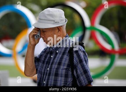 Kohei Jinno, 87 anni, costretto a lasciare la sua casa due volte prima delle Olimpiadi del 1964 e del 2020 per far posto alla costruzione dello stadio principale, strofina gli occhi davanti al monumento degli anelli olimpici fuori dal Museo Olimpico del Giappone vicino allo Stadio Nazionale, Lo stadio principale per i Giochi Olimpici di Tokyo del 2020 che sono stati rinviati al 2021 a causa della pandemia della malattia del coronavirus (COVID-19), a Tokyo, Giappone, 24 giugno 2021. Foto scattata il 24 giugno 2021. REUTERS/Issei Kato