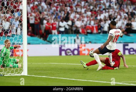 Il danese Simon Kjaer (a destra) segna e il proprio gol sotto la pressione di Raheem Sterling inglese per dare all'Inghilterra il primo gol della partita durante la partita semifinale UEFA Euro 2020 al Wembley Stadium di Londra. Data immagine: Mercoledì 7 luglio 2021.