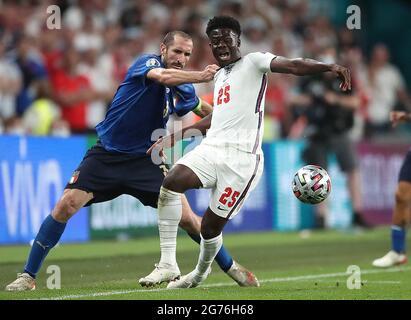 L'italiano Giorgio Chiellini (a sinistra) tira indietro il Bukayo Saka inglese durante la finale UEFA Euro 2020 al Wembley Stadium di Londra. Data immagine: Domenica 11 luglio 2021.
