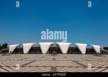 Il 10 giugno 2021 si può prendere il sole nella piazza di fronte allo stadio di atletica progettato da Masachika Murata all'interno del Parco Olimpico di Komazawa, Tokyo. Il parco è stato costruito per le Olimpiadi del 1064 e rimane un popolare luogo di svago. Robert Gilhooly foto