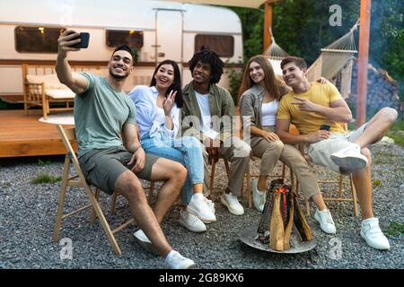 Diversi giovani amici che prendono selfie vicino al fuoco di sera, utilizzando smartphone, seduti accanto al camper durante il viaggio in campeggio