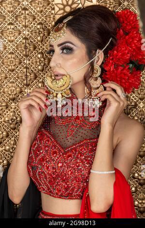 Bella sposa asiatica in abito rosso nel salone