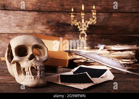 Natura morta con teschio umano, libro retrò e tubetto su sfondo di legno
