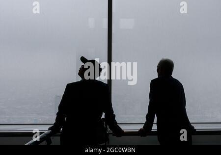 Due turisti maschili si avvistano dalla piattaforma di osservazione al 45° piano della Tokyo Metropolitan Government Tower a Shinjuku in una giornata piovosa, Tokyo,