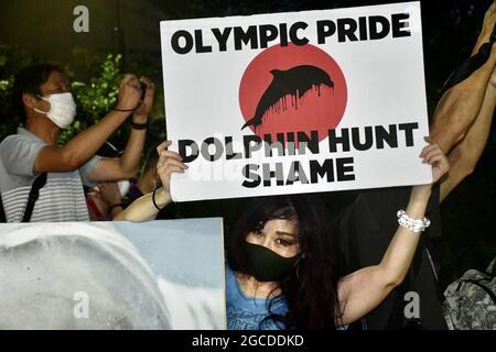 Tokyo, Giappone. 8 agosto 2021. Un dimostratore tiene un cartello con il messaggio 'Olympic Pride - Dolphin Hunt Shame' durante una protesta fuori dallo Stadio Nazionale del Giappone (noto anche come Stadio Olimpico) prima della cerimonia di chiusura dei Giochi Olimpici estivi del 2020. I Giochi Olimpici si sono tenuti in mezzo alla pandemia COVID-19. I manifestanti chiedono alle autorità di annullare i Giochi Paralimpici estivi del 2020 che si svolgeranno a Tokyo dal 24 agosto al 5 settembre. Credit: Igor Belyayev/TASS/Alamy Live News