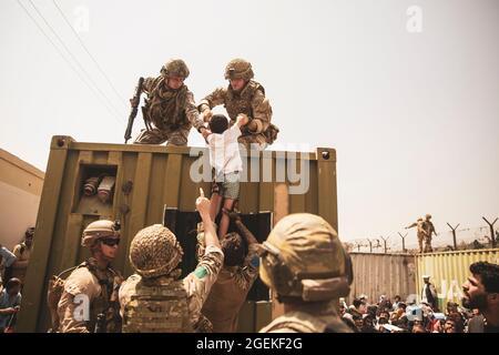Kabul, Afghanistan. 20 ago 2021. Soldati britannici, turchi e statunitensi aiutano un bambino a garantire la sicurezza durante l'evacuazione dei civili all'aeroporto internazionale Hamid Karzai, parte dell'operazione Allees Refuge 20 agosto 2021 a Kabul, Afghanistan. Credit: Planetpix/Alamy Live News
