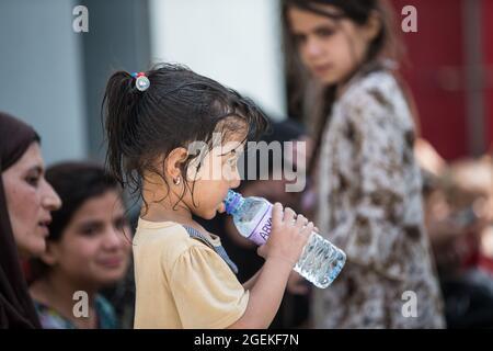 Kabul, Afghanistan. 20 ago 2021. Un bambino afghano beve acqua fresca fornita durante l'evacuazione dei civili all'Aeroporto Internazionale Hamid Karzai, parte dell'operazione Rifugi Alleati 20 agosto 2021 a Kabul, Afghanistan. Credit: Planetpix/Alamy Live News