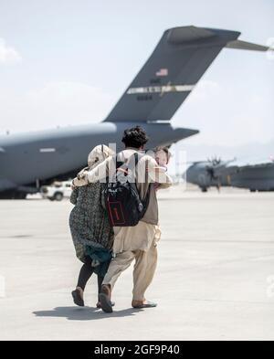 Kabul, Afghanistan. 22 agosto 2021. Una famiglia afghana cammina verso un aereo della forza aerea statunitense C-17 Globemaster III per l'evacuazione all'aeroporto internazionale Hamid Karzai durante l'operazione Allies Refuge 24 agosto 2021 a Kabul, Afghanistan. Credit: Planetpix/Alamy Live News