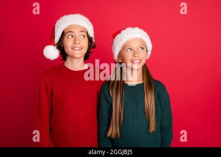 Ritratto di due amici allegri e attraenti che indossano un cappellino festale che fantasiizza isolato su sfondo rosso brillante