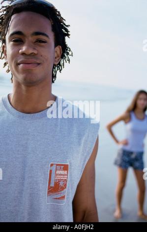 Ritratto di un adolescente in piedi presso la spiaggia con una ragazza adolescente dietro di lui Foto Stock