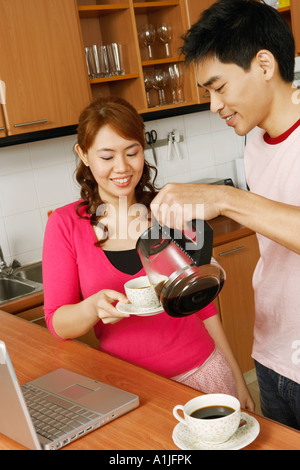 Close-up di una metà uomo adulto che serve tè a una giovane donna in un banco di cucina Foto Stock