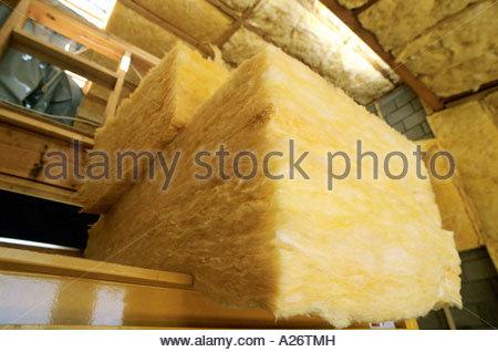 R38 isolamento in fibra di vetro essendo installato nel tetto nel nuovo stile loft home in costruzione Foto Stock