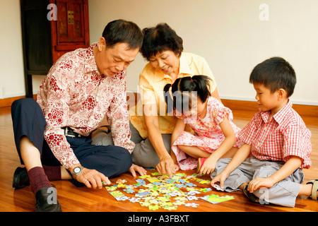 Ragazza e un ragazzo giocando puzzle con i loro nonni Foto Stock