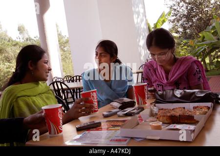 Giovani donne indiane che lavora nel settore IT per Infosys mangia fast food occidentali durante una pausa pranzo Foto Stock