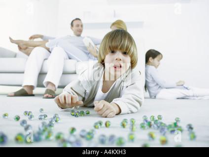 Ragazzo disteso sul pavimento la riproduzione di marmi, i genitori e la sorella seduta in background Foto Stock