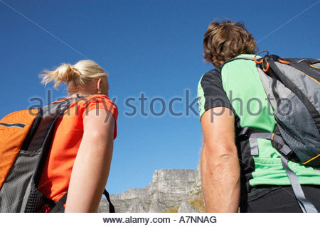 Arrampicata su roccia giovane con zaini guardando al rock in distanza vista posteriore stretta fino a basso angolo Foto Stock