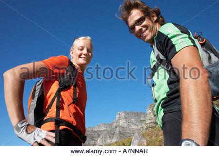Arrampicata su roccia giovane prendendo break sorridente rock in distanza vista laterale verticale a basso angolo Foto Stock