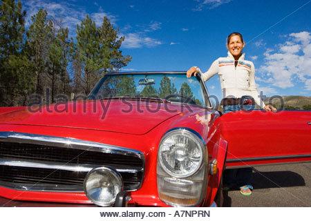 Giovane donna in piedi accanto al rosso convertibili auto sulla strada di campagna sorridente vista anteriore verticale Foto Stock