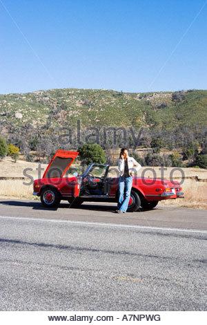 La donna in piedi accanto al rosso convertibili auto sulla strada di campagna riscontrando problemi con la macchina Foto Stock
