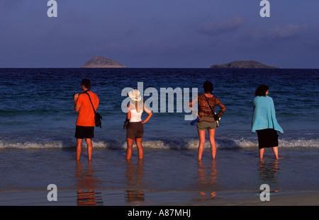 4 persone a guardare per tartarughe isola Galapagos Ecuador Sud Ameriaca Foto Stock