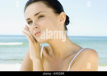 Donna di toccare la faccia con il dorso della mano, mare sullo sfondo, la testa e le spalle Foto Stock