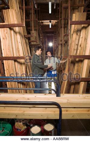Gli uomini guardando attraverso il legname in negozio Foto Stock