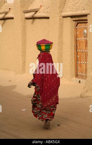 Una Donna vestita in abiti tradizionali e portante una pentola sulla sua testa, passeggiate passato la moschea di Foto Stock