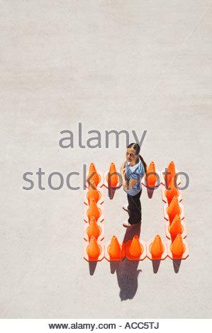 Donna dentro la casella di traffico coni Foto Stock