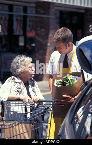 Caucasica drogheria teenage clerk aiutando senior con negozi di generi alimentari Foto Stock