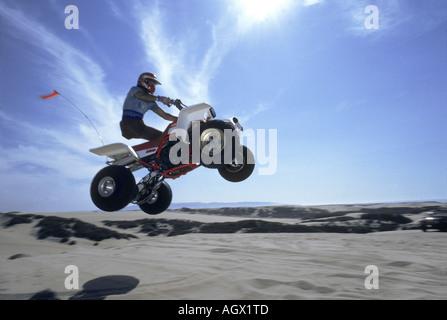 Un veicolo fuoristrada prende all'aria e vola oltre le dune di sabbia in una spiaggia della California Foto Stock