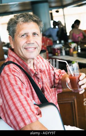 Ritratto di un uomo anziano con in mano un bicchiere di succo di frutta e sorridente Foto Stock