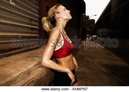 Donna runner in appoggio contro la parete Foto Stock