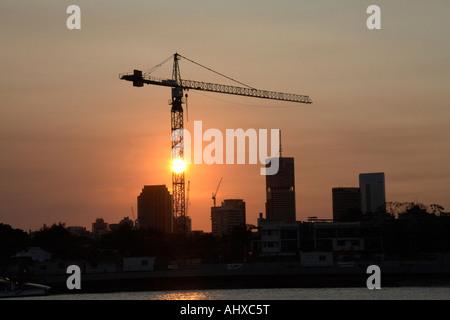 Gru da cantiere in serata silhouette al tramonto vicino a Teneriffe Queensland Brisbane Qld Australia Foto Stock