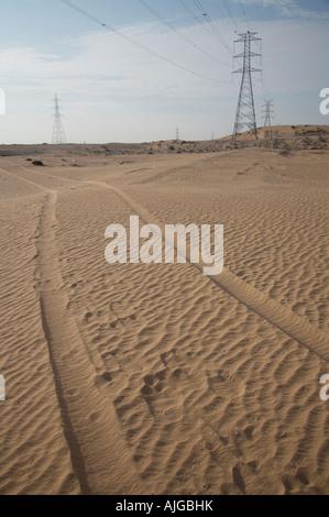 Tracce di pneumatici che conducono fuori nel deserto di sabbia negli Emirati arabi uniti emirati arabi uniti medio Foto Stock