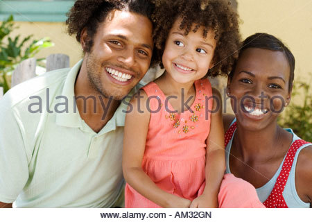 Coppia col giovane ragazza sorride all'aperto Foto Stock