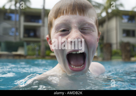 Ragazzo in piscina esterna rendendo divertente volto Foto Stock